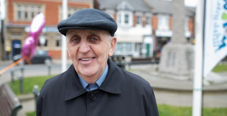 An elderly man wearing a hat smiling at the camera