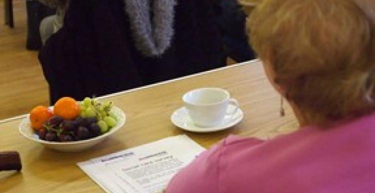 Person sitting at table with a coffee and Healthwatch literature